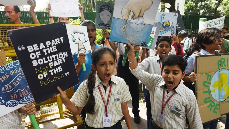 School students and members of the general public gather with placards while raising slogans to save the environment in front of the Ministry of Housing and Urban Affairs in New Delhi.
