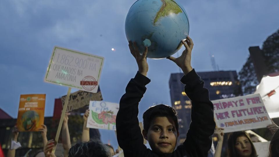 A boy holds up a small globe during a global protest on climate change in Sao Paulo, Brazil. Across the globe, hundreds of thousands of people took to the streets Friday to demand that leaders tackle climate change in the run-up to a UN summit.