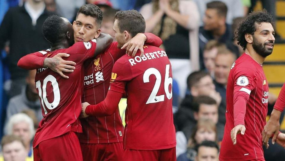 Liverpool's Roberto Firmino, center, celebrates with teammates Sadio Mane, left, and Andrew Robertson.