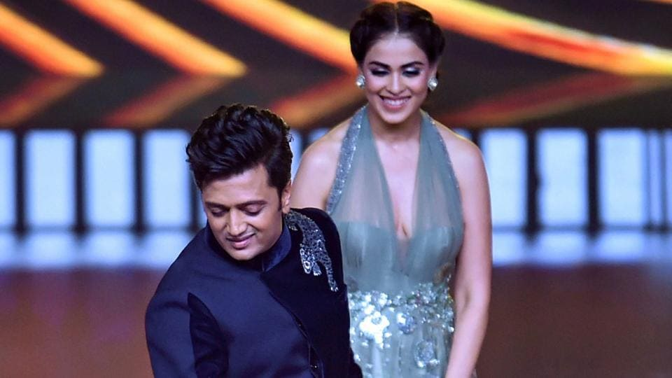 Riteish Deshmukh performs as wife Genelia D'Souza looks on at the 20th IIFA awards ceremony, in Mumbai.