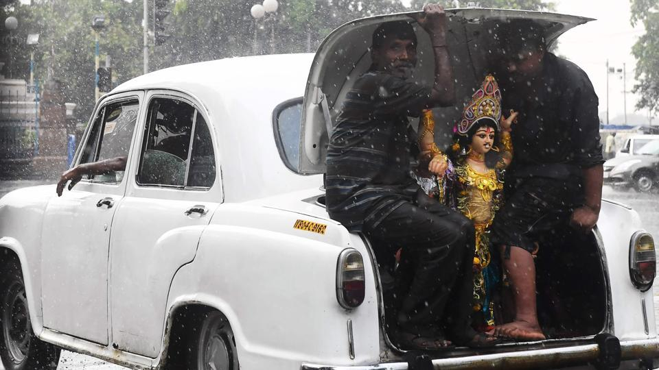 Devotees sit in the boot of a Hindustan Ambassador car with an idol of the Hindu deity Vishwakarma as they transport it in the rain for an immersion ceremony in Kolkata, West Bengal. (Dibyangshu Sarkar / AFP)