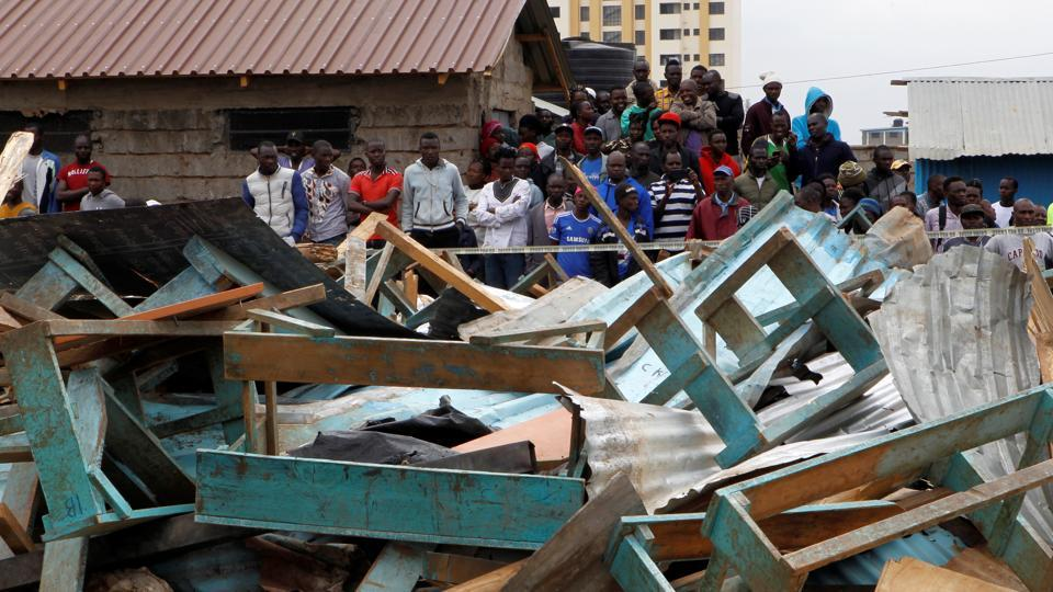 Kenyan people gather at the site of a collapsed school classroom, in Nairobi, Kenya.