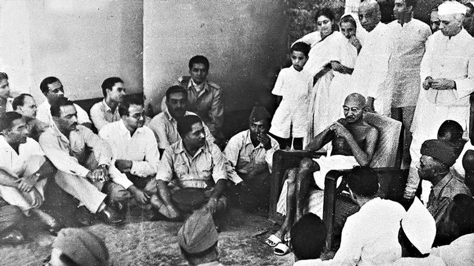 Mahatma Gandhi flanked by Vallabhbhai Patel and Jawaharlal Nehru (standing behind him) with officers of the Indian National Army in Delhi, April 1946.
