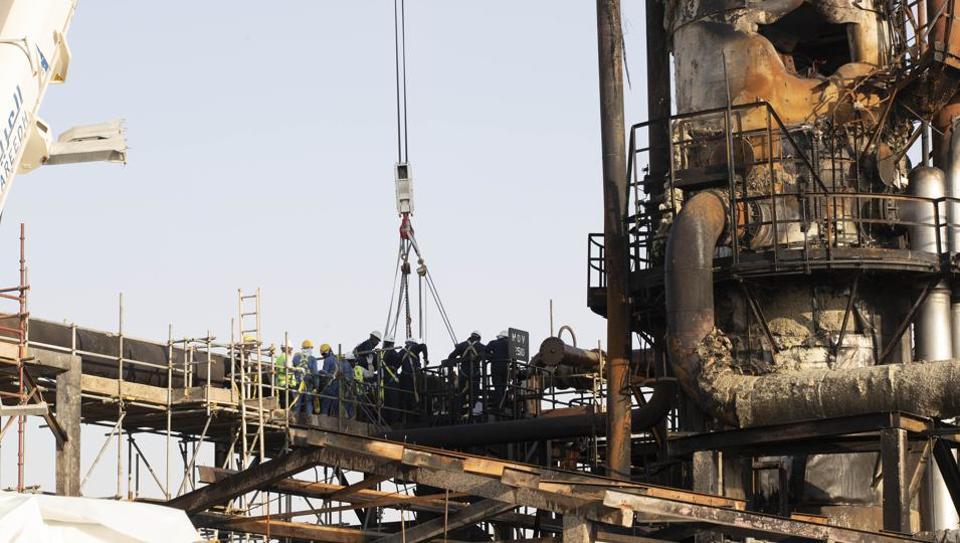 Workers repair a damaged refining tower at Saudi Aramco's Abqaiq crude oil processing plant following a drone attack in Abqaiq, Saudi Arabia.