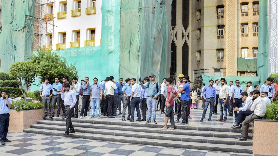 People come out of the Ambadeep Building at Connaught Place during a tremor in New Delhi, Tuesday, Sept. 24, 2019.