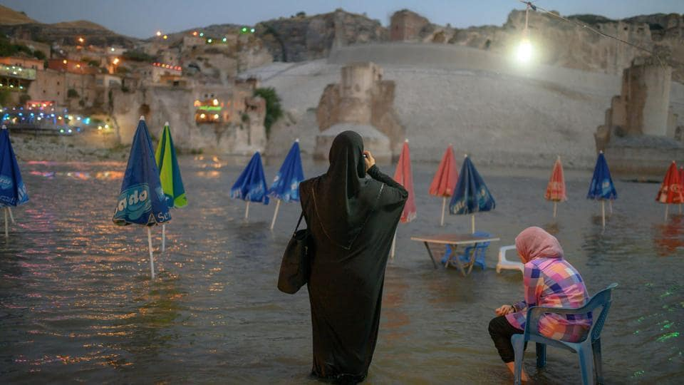 A woman takes a picture of Hasankeyf, on the banks of the Tigris. At first glance all is as normal in this Turkish town which as seen the Romans, Byzantines, Turkic tribes and Ottomans leave their mark over its 12,000 years of inhabitation. But Hasankeyf is disappearing. An artificial lake, part of the Ilisu hydroelectric dam project, is swallowing it up. The dam, which will be Turkey's second largest, has been built further downstream the Tigris. (Bulent Kilic / AFP)