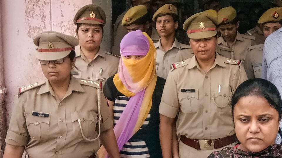 The woman law student (face covered), who alleged BJP leader Chinmayanand of sexual misconduct and harassment, is seen outside a government hospital after a medical examination, in Shahjahanpur, Wednesday, Sept. 25, 2019. The student was arrested today morning by the Special Investigation Team.