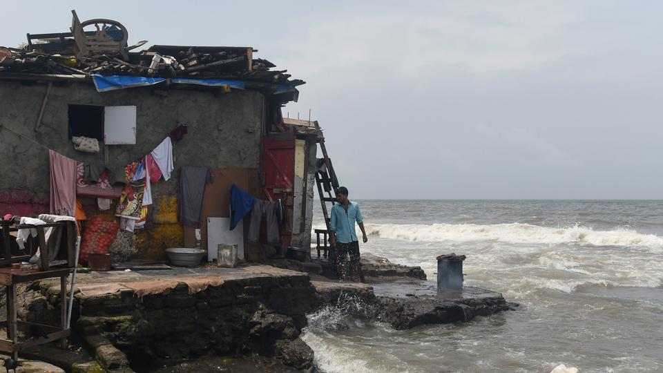 """A man stands next to a home built by the sea during high tide in Mumbai. During the monsoon, near-daily storms regularly flood Dharavi, home to some of the city's most vulnerable residents. """"The situation has been getting worse every year, with our homes knee-deep in water,"""" Venkatesh Nadar, 38, who has lived in the shanty settlement his entire life, told AFP. (Punit Paranjpe / AFP)"""