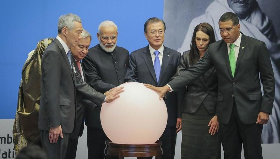 Singapore PM Lee Hsien Loong, from left to right, Bangladesh PM Sheikh Hasina, United Nations Secretary-General Antonio Guterres, PM Narendra Modi, South Korea President Moon Jae-in, New Zealand PM Jacinda Ardern and Jamaica's PM Andrew Holness place hands on a light ball symbolizing earth for a special event commemorating the 150th anniversary of Mahatma Gandhi, during the United Nations General Assembly, Tuesday.