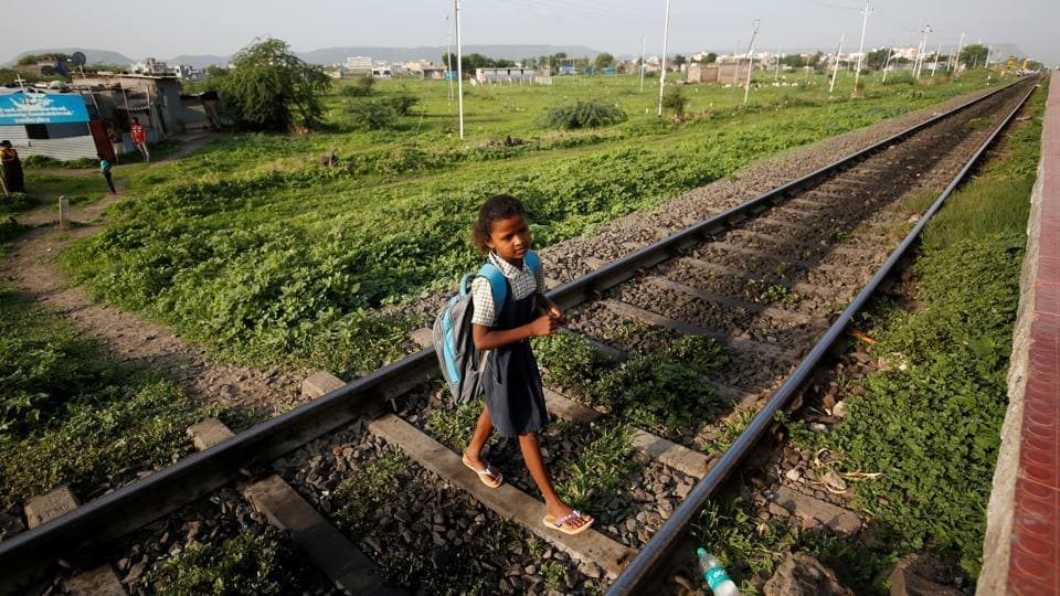 Sakshi Garud crosses the railway tracks at Mukundwadi railway station on her way to school, in Aurangabad. While their classmates set off to play after school each day, nine-year-old Sakshi Garud and her neighbour Siddharth Dhage, 10, are among a small group of children who take a 14-km return train journey from their village in Maharashtra to fetch water. (Francis Mascarenhas / REUTERS)