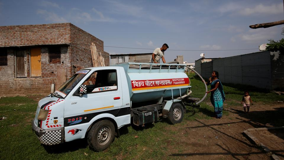 A woman takes hold of a pipe from a water tanker in Aurangabad. More than 100 families in Garud and Dhage's neighbourhood do not have access to piped water and many depend on private water suppliers, who charge up to 3,000 rupees ($42) for a 5,000-litre tanker during summer months. (Francis Mascarenhas / REUTERS)