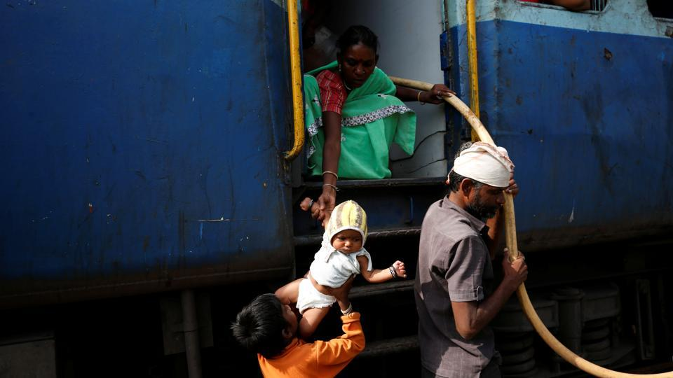 "Jyoti Dhage passes her daughter Akansha to her son Siddharth at Aurangabad railway station. ""Some people help me, sometimes they complain to railway officials for putting pitchers near the door. If we don't put them near the door, we cannot take them out quickly when the train stops,"" Siddharth said.  (Francis Mascarenhas / REUTERS)"