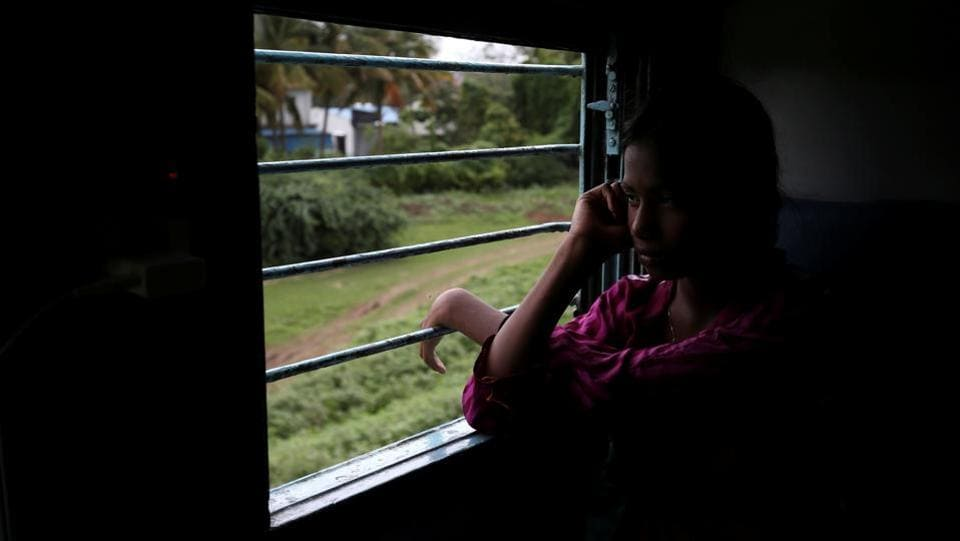 Manju Gaikwad, 11, looks out of the window of a train on her way back home to Mukundwadi railway station. When the train returns them to Mukundwadi, they have just under a minute to disembark. At times, Dhage's mother, Jyoti, is waiting at the station to help. (Francis Mascarenhas / REUTERS)