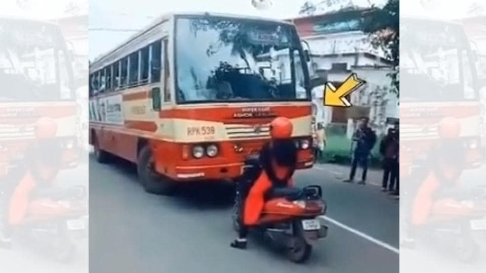 The image shows the woman standing in front of the bus.
