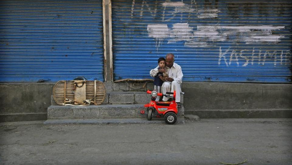 A man feeds a child outside a closed shop during curfew hours in Srinagar, Jammu and Kashmir. As the disputed Himalayan region continues to reel under unprecedented lockdown for the 53rd consecutive day, the children of the region have been the most affected. The crisis has upended the education of millions of children, and many have been caught up in street violence. (Mukhtar Khan / AP)