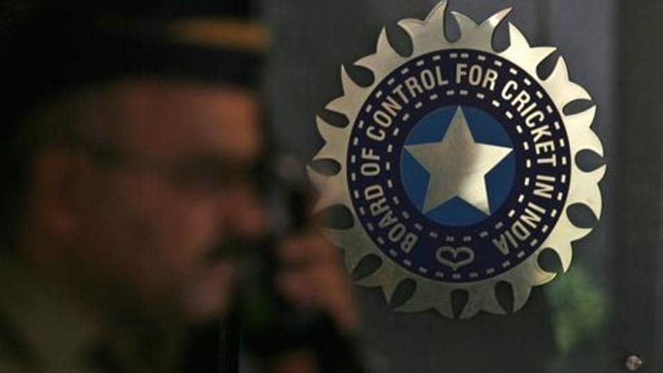 A policeman walks past a logo of the Board of Control for Cricket in India (BCCI).