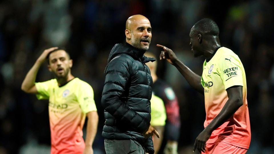 Manchester City manager Pep Guardiola celebrates with Benjamin Mendy.