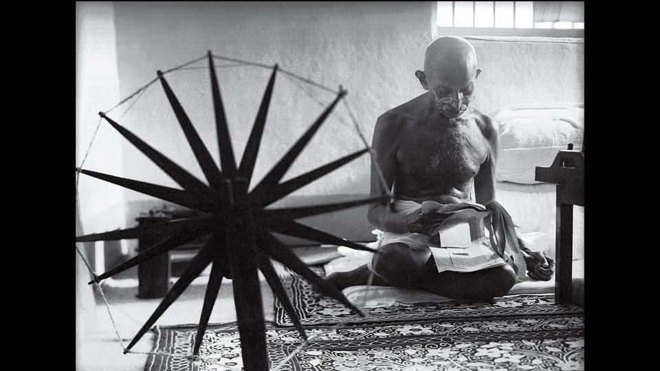 A 1964 photohraph of Gandhi taken by Margaret Bourke White shows him reading clippings with a charkha in the foreground.