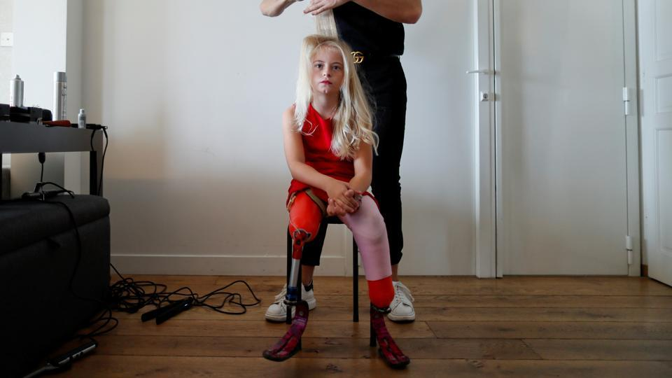 Model Daisy-May Demetre, 9 year-old double amputee who will walk the runway during Paris Fashion Week, gets her hair done a day before the show of luxury children's wear label Lulu et Gigi in Paris.