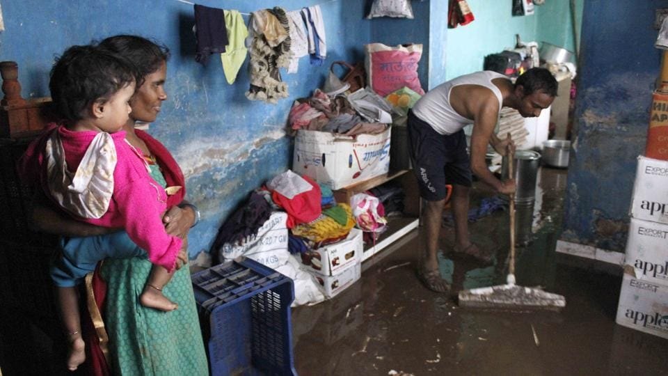 A man clears his home of water at Ambegaon Budruk in Pune. More than 28,000 people have been evacuated from low-lying areas. The Army rescued 300 people, including some stranded on rooftops and in the trees, from Solapur Road area, a defence spokesperson said. (Ravindra Joshi / HT Photo)