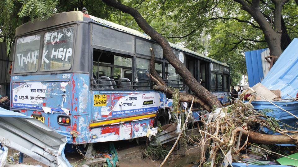 Residents of Amrapali Society rescued around 40 people from this PMPML bus on Narhe road after heavy rain on Thursday. At least 21 persons were reported killed and nine missing in various rain-related incidents in Pune, Jalgaon and Nashik, officials said on Thursday. Of the total fatalities, 14 deaths took place in Pune district, six in Jalgaon and one in Nashik. (Ravindra Joshi / HT Photo)