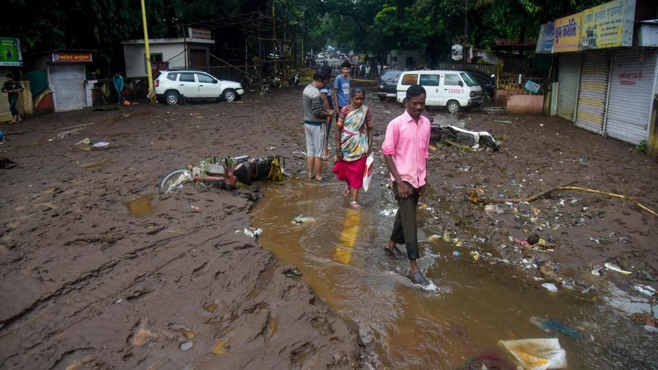 People cross a muddied street near Tangewale colony in Pune. Incidents of wall collapse were also recorded in Pune city. When asked if unauthorized constructions exacerbated the situation, Pune commissioner Saurabh Rao said action will be taken against such structures. (Sanket Wankhade / HT Photo)