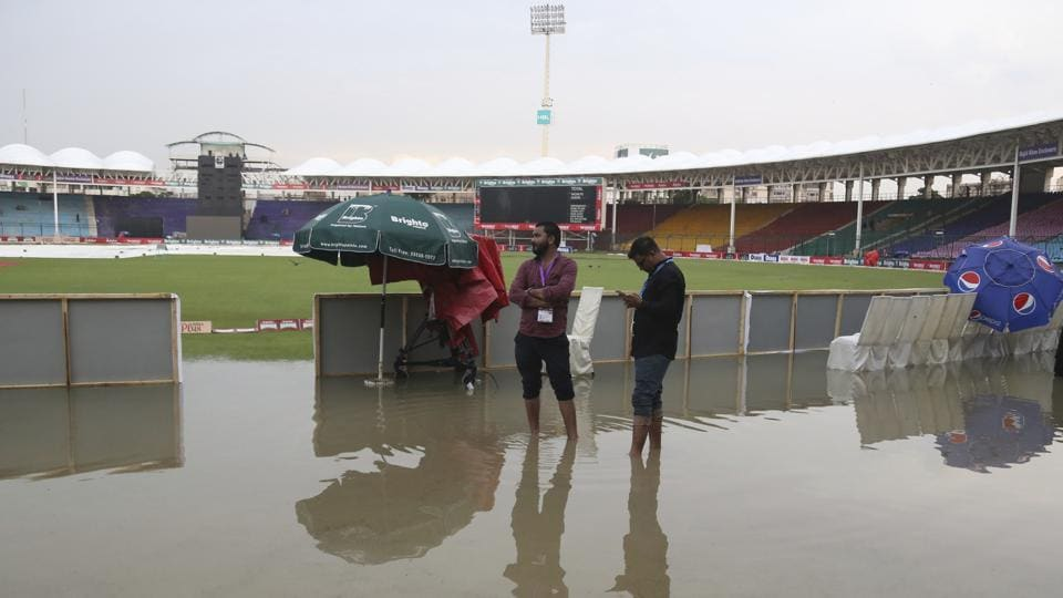 Officials stand at the National Stadium after rain in Karachi, Pakistan.