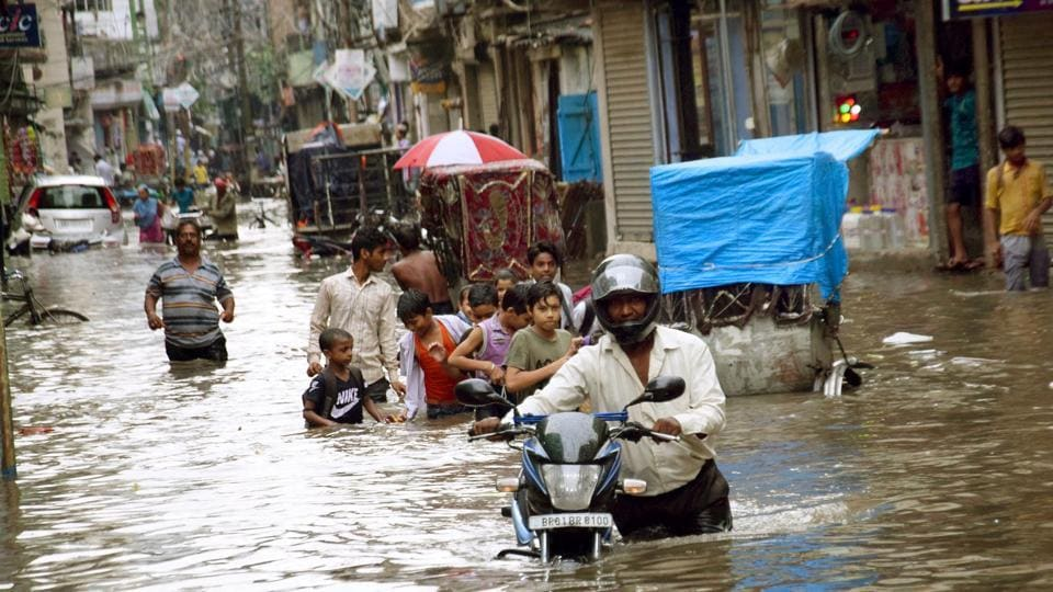People seen crossing waterlogged area at Langartoli in Patna after heavy rains. Water has entered many residential areas and hospitals and is causing trouble for the general population.