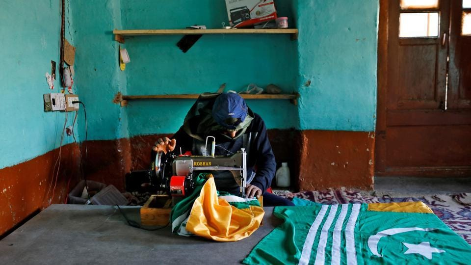 Mushtaq Wani, a 35-year-old tailor, sews Azad (Independent) Kashmir flags inside his house in Anchar neighbourhood during restrictions.
