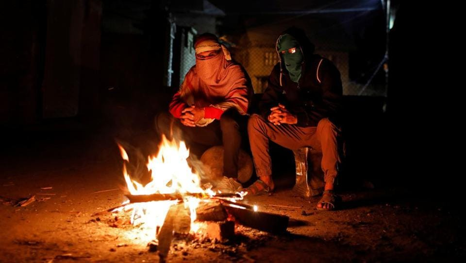 As night falls, groups of youths, many wearing masks and armed with stones and tree branches, are huddled around bonfires, sipping tea provided by neighbours. They keep vigil in fear that the police will enter their homes. (Danish Siddiqui / REUTERS)