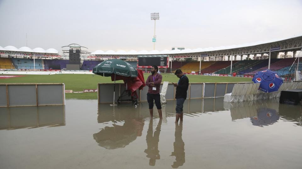Officials stand at the National Stadium after rain in Karachi, Pakistan, Friday, Sept. 27, 219. Heavy rain has delayed the start of the first one-day international between Pakistan and Sri Lanka. An unusual spell of rain in the southern port city of Karachi during this time of the year left the cricket ground completely waterlogged on Friday.