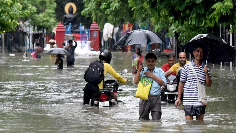 People wade through a flooded street aftert heavy rainfall in Patna on Saturday.