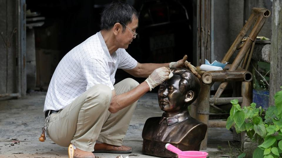 "Feng works on a bust portraying late Chinese chairman Mao Zedong outside his studio in Jingdezhen. ""I make statues of whoever is in power. I've done Mao, Deng Xiaoping and Jiang Zemin,"" he said. Business has been brisk this year as China prepares to celebrate in October the 70th anniversary of its founding as the People's Republic of China. (Jason Lee / REUTERS)"