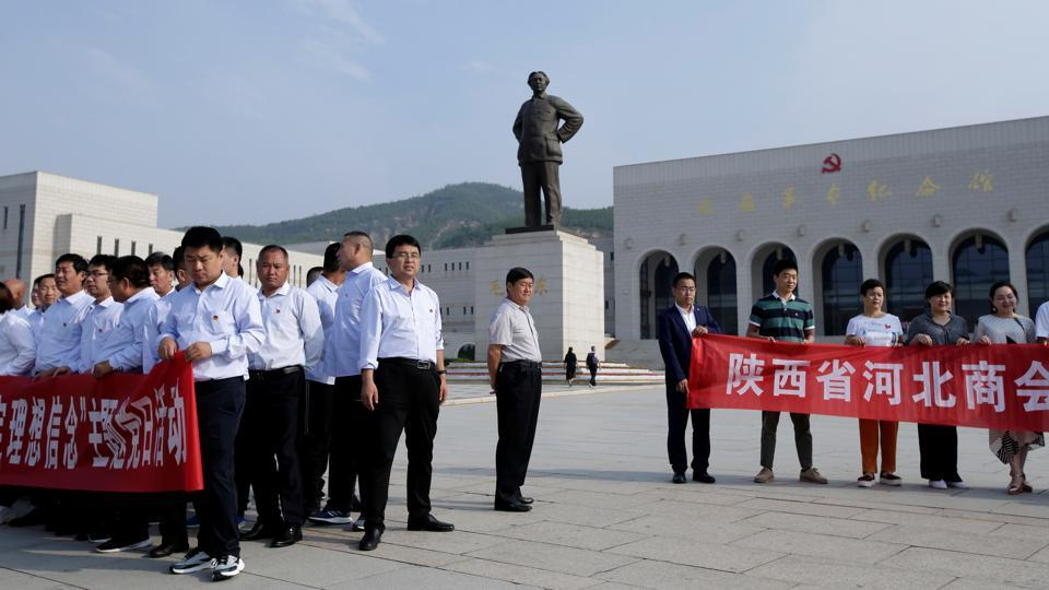 "People hold banners for group photos in front of a statue of late Chinese chairman Mao Zedong outside Yanan Revolutionary Memorial Museum in Yanan. ""By and large he has an image that no one else can match in Chinese official media,"" Xiao said. Still, the government has actively sought to ban adoring songs and the use of 'Uncle Xi' in state media.  (Jason Lee / REUTERS)"