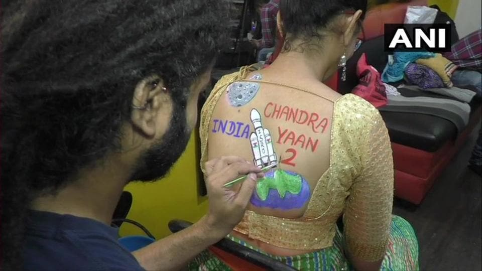 As a part of Navratri 2019 preparation, a woman is getting body paint tattoo.