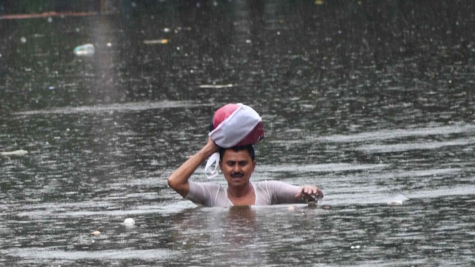 A man wades through a flooded street after heavy rainfall in Patna on Sunday. (ANI PhoTO)