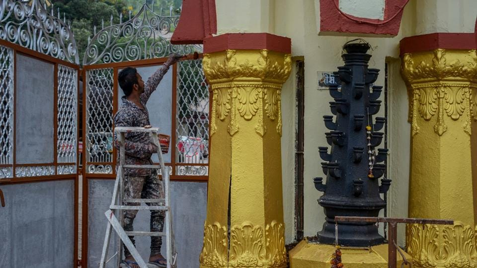 A worker seen painting a pillar at the  Chatuhshrungi temple prior to Navratri.