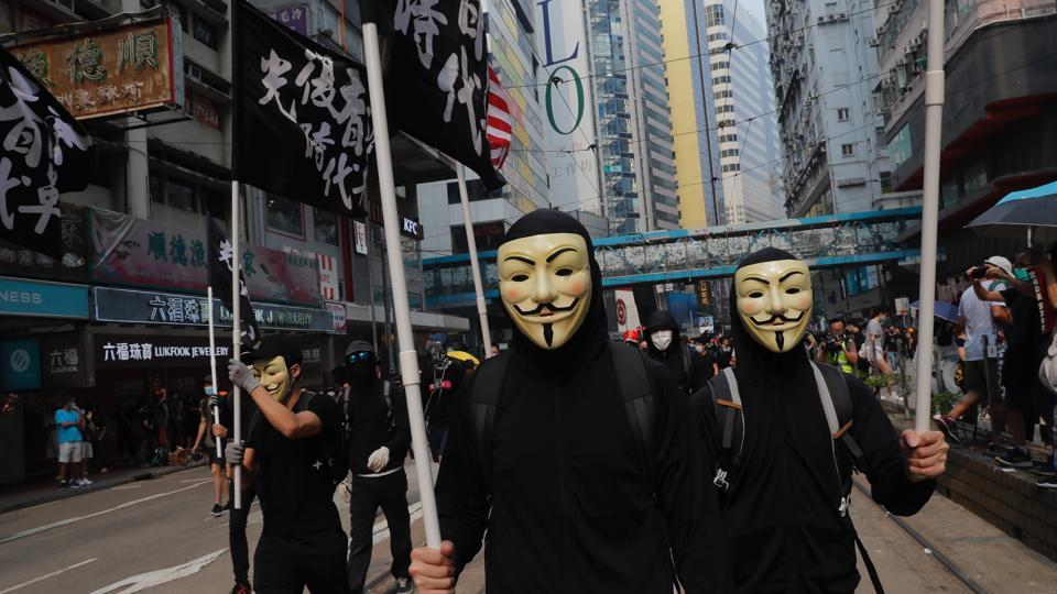 Protestors march on streets wearing masks in Hong Kong .