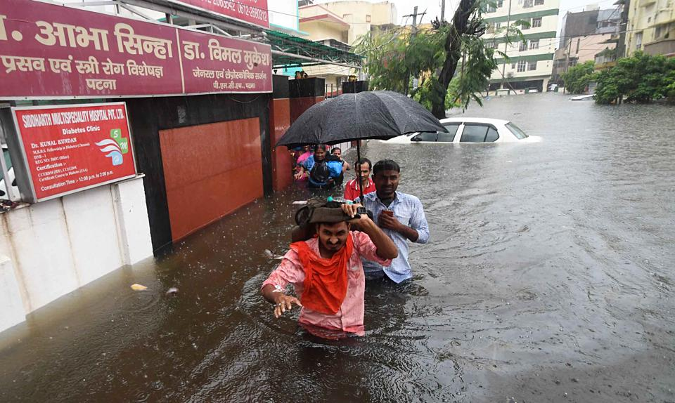 A patient along with his attendant and nursing staff waits for a rescue team to arrive on a flooded street in Patna. As many as 25 people have been killed in Bihar in the last 24 hours. (ani photo)