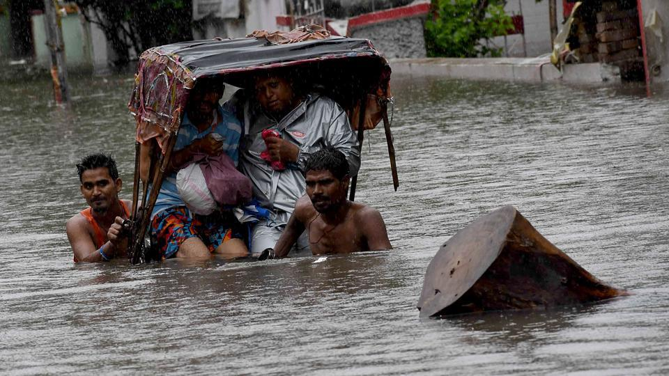 A rickshaw puller wades through a flooded street after heavy rainfall, in Patna.