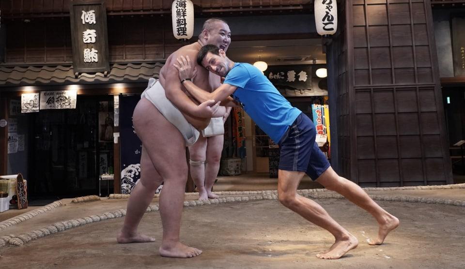 Novak Djokovic in a match with a sumo wrestler in Japan