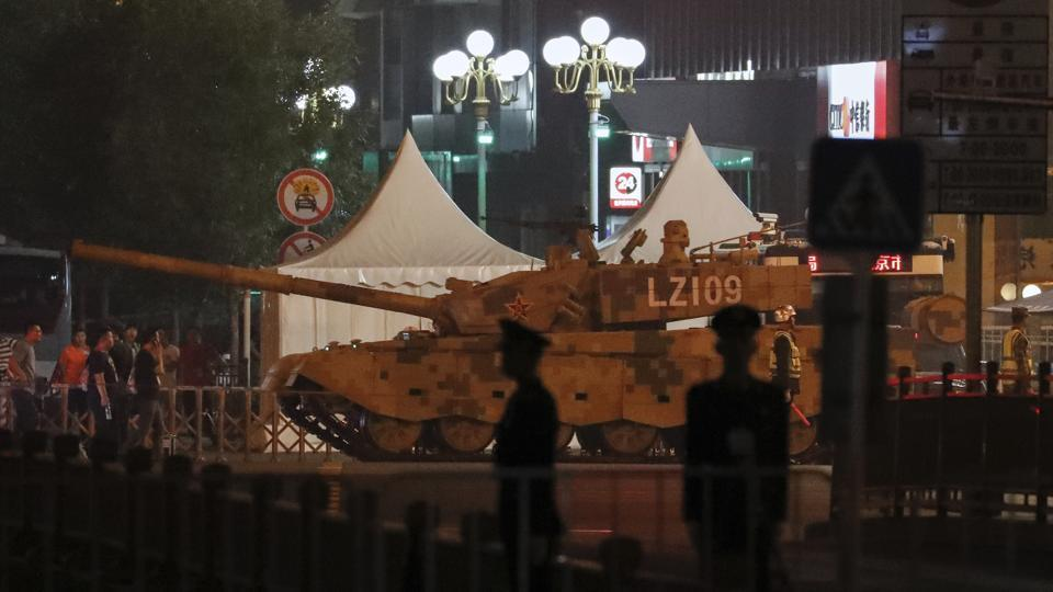 People watch a military tank passes along the Jianguomenwai Avenue in Beijing on Saturday. Many of the streets in the central part of China's capital were being shut down this weekend for a rehearsal for what is expected to be a large military parade on Oct. 1 to commemorate the 70th anniversary of Communist China.