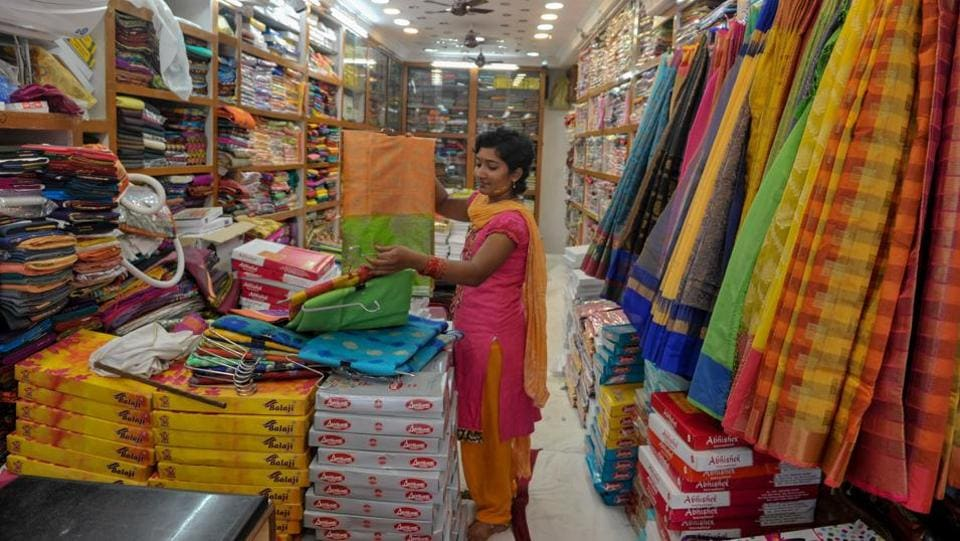 A vendor arranges sarees inside at a shop ahead of upcoming Hindu 'Dushhera-Vijaya Dashami' festival, marking the end of 'Durga Puja' that honours goddess Durga's victory, in Hyderabad, Telangana. E-commerce giants Amazon and Walmart-backed Flipkart kicked off a crucial battle for shoppers on Sunday ahead of the festive season as retailers search for a much-needed boost to sales in a slowing economy. (Noah Seelam / AFP)