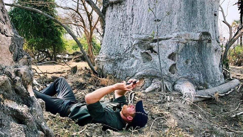 Prince Harry lying on the ground as he points his camera up towards the sky to capture a stunning still.