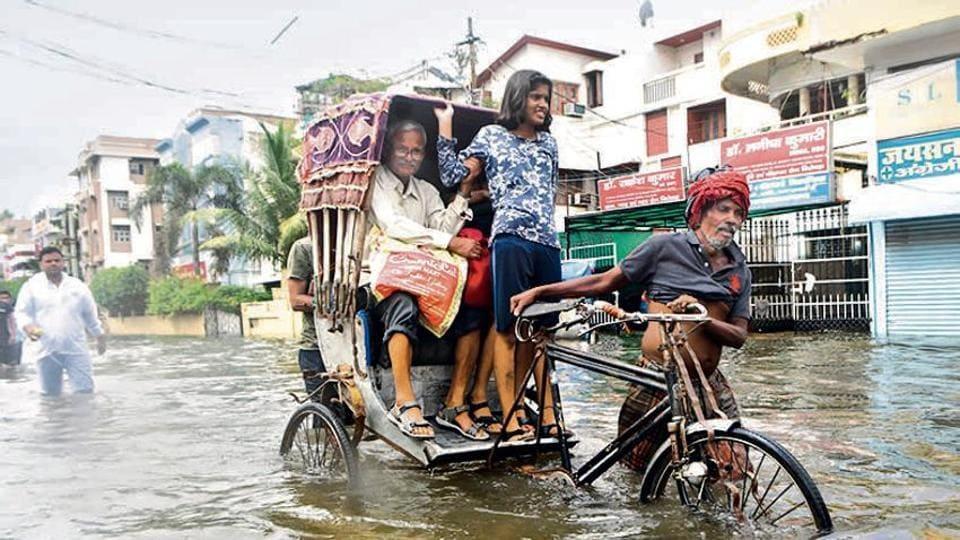 A cycle rickshaw driver moves through waterlogged roads of Patna.