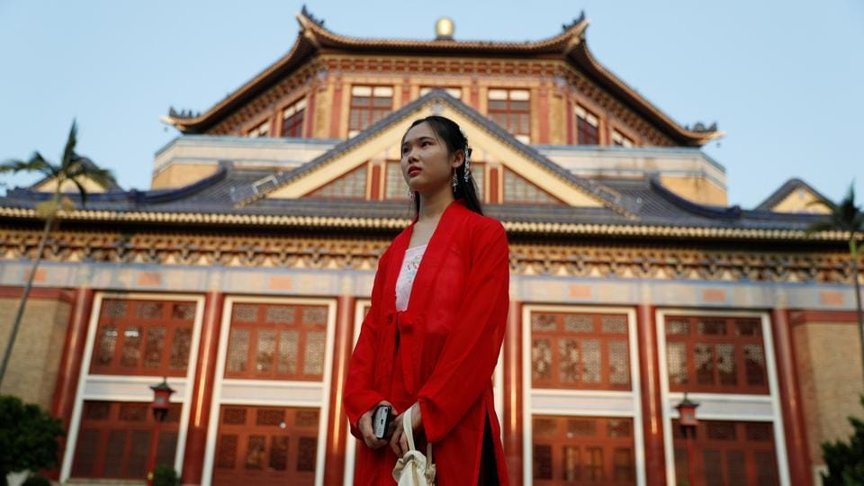 A woman dressed in traditional clothes stands in front of Sun Yat-sen Memorial hall in Xinji district in Guanghzou. Life on the city's fringes can be hard, with house prices among China's highest and poorer elderly residents forced to sort rubbish to earn a living. (Jorge Silva / REUTERS)