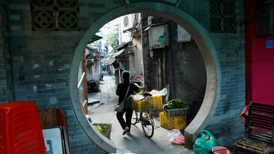 A woman pushes a bike in the city's old district of Liwan in Guanghzou. Life on the city's fringes can be hard, with house prices among China's highest and poorer elderly residents forced to sort rubbish to earn a living. (Jorge Silva / REUTERS)