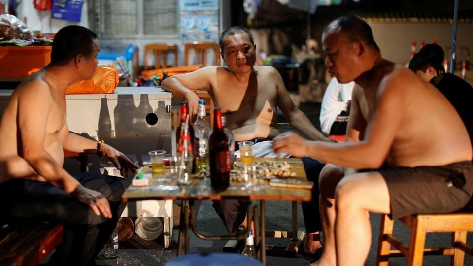 Men drink and chat outside of a shop in the traditional neighbourhood of Yuexiu in Guanghzou. By the evening, hawker stalls and small massage parlours light up dim alleys that come alive with chatter and beer drinking as friends try to beat the sultry summer heat. (Jorge Silva / REUTERS)