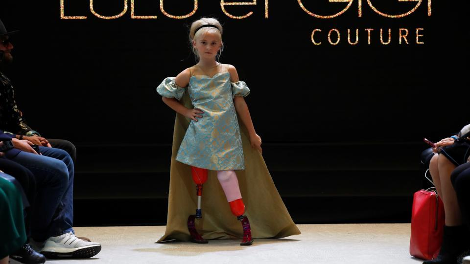 Daisy-May Demetre presents a creation by Designer Eni Hegedus-Buiron for luxury children's wear label Lulu et Gigi during Paris Fashion Week inside Eiffel Tower, in Paris, France. Nine-year-old Demetre, whose legs were amputated due to a birth defect, became the first double amputee to walk the runway the prestigious show. (Gonzalo Fuentes / REUTERS)