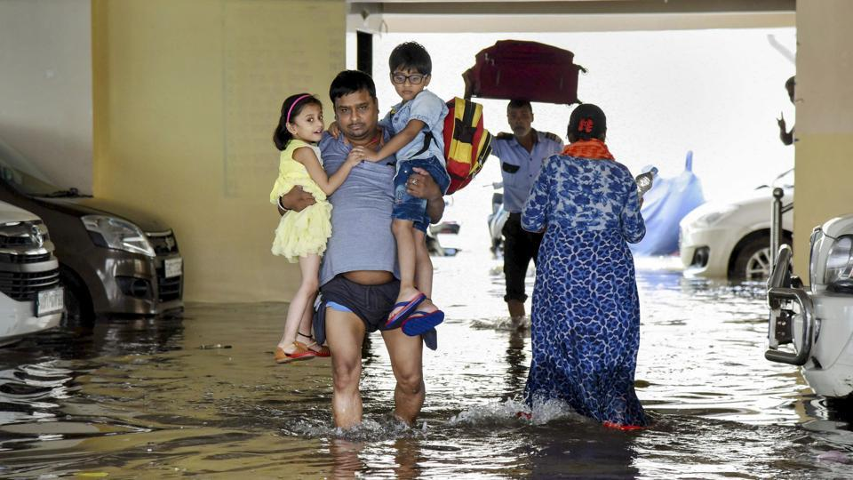 A man, carrying children from school, wades through flood-water in Rajendra Nagar area of Patna.